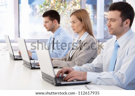 Young professionals busy by working, using laptop in meeting room. - stock photo