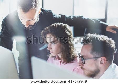 Young professionals work in modern office.Project managers team discussing new idea.Business crew working with startup.Using desktop computer. Blurred,film effect. Horizontal