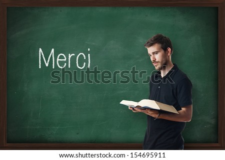 Young professor of French writing Merci on chalkboard