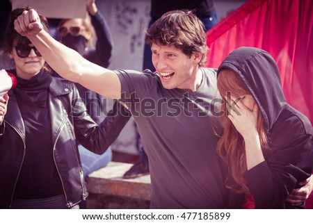 Young protester with his girlfriend, shouting slogans during a demonstration