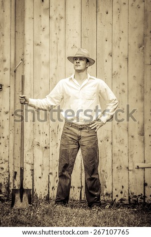 Young Proud Farmer standing up in front of Barn - stock photo