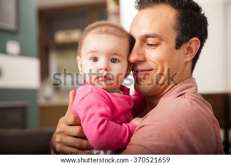 Young proud single dad holding his baby daughter close to him while relaxing at home - stock photo