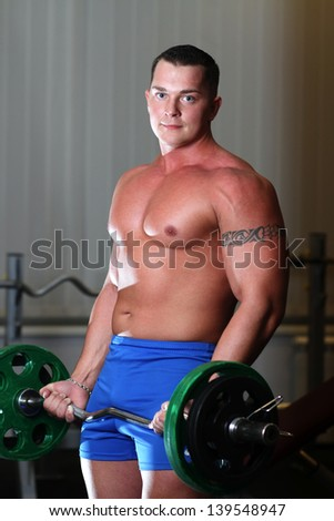 Young pumped powerlifter with a tattoo on his bicep exercising in gym