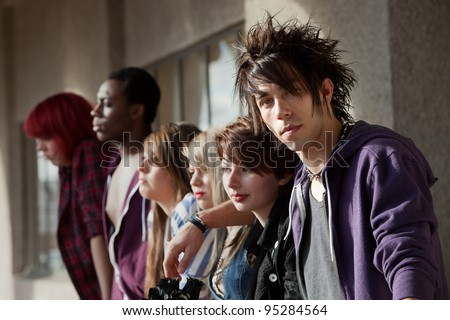 Young punk boy looks at the camera as his friends look away into the distance.