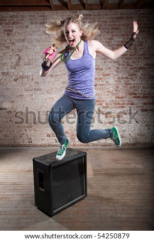 Young punk rocker jumps from a speaker in front of a brick background - stock photo