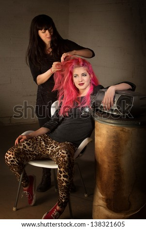 Young punk rocker leaning back with hair stylist working - stock photo