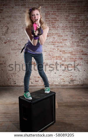 Young punk rocker on a speaker in front of a brick background - stock photo