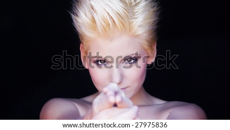 Young punk woman aiming with hands over black background. - stock photo