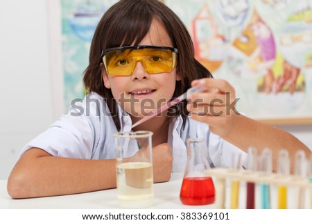 Young pupil conducting a simple chemical experiment in elementary science class - stock photo