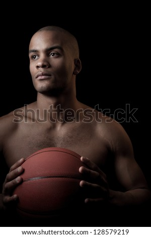 young purposeful black athlete holding basketball ball isolated on black background - stock photo