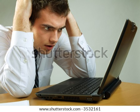 Young puzzled business man or student on laptop working or reading mail at the table