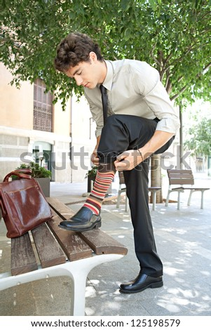 Young quirky businessman pulling up his socks while stepping on a wooden bench in the city, outdoors. - stock photo