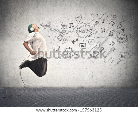 young rapper jumps and listens to music - stock photo