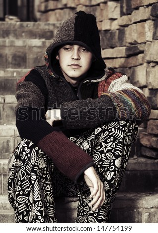 Young rastafarian man sitting on the steps - stock photo
