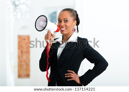 Young realtor in apartment advertising it with a megaphone - stock photo