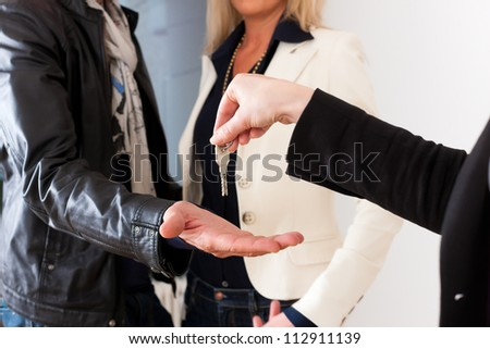 Young realtor is giving the keys to an apartment to a young couple, maybe the purchaser or the tenants - stock photo