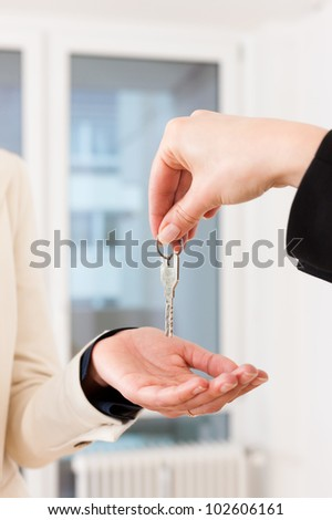 Young realtor is giving the keys to an apartment to the tenant, close-up on keys and hands - stock photo