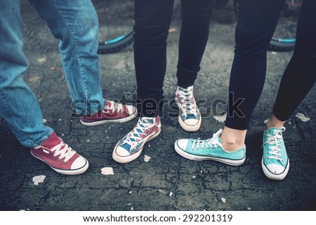 Young rebel teenagers wearing casual sneakers, walking on dirty concrete. Canvas shoes and sneakers on female adults  - stock photo