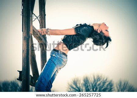 young rebel woman in blue jeans and leather jacket outdoor shot on old metal construction hot sunny day - stock photo