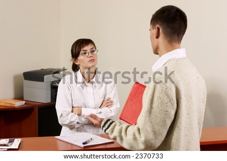 young receptionist at her desk helping a customer