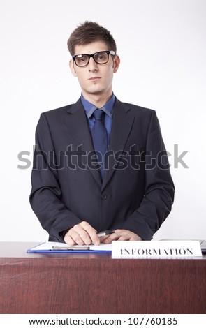Young receptionist at information desk. - stock photo