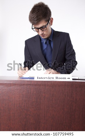 Young receptionist showing direction to interview room. - stock photo