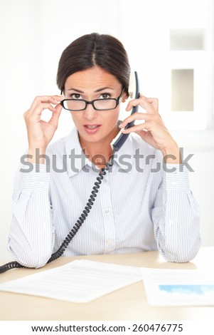 Young receptionist with spectacles conversing on the phone while looking surprised at her workplace - stock photo