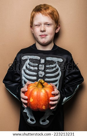 Young red hair boy holding a small pumpkin for Halloween. Studio portrait on brown background - stock photo