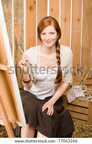 Young red-hair romantic woman in barn painting on canvas