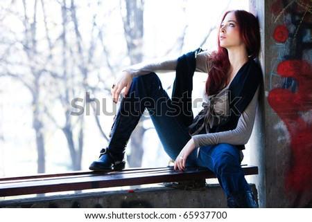 young red hair woman in casual clothes sit on banch, outdoor shot