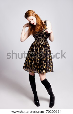 young red hair woman in glittering dress, full body shot, studio shot - stock photo