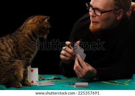 Young red-haired bearded man in glasses playing poker with tabby cat sitting at gaming table on black background - stock photo