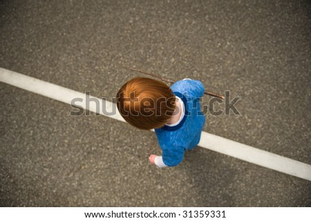 Young, red-haired boy walking along solid white road line. - stock photo