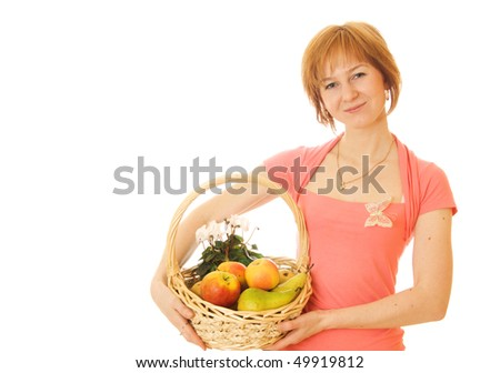 Young red haired caucasian woman holding backet full of fresh fruits isolated on white background