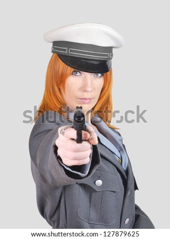 young red-haired girl in uniform with gun, on a gray background - stock photo