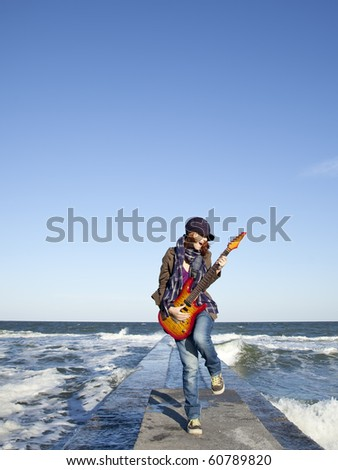 Young red-haired girl play on guitar at windy day.
