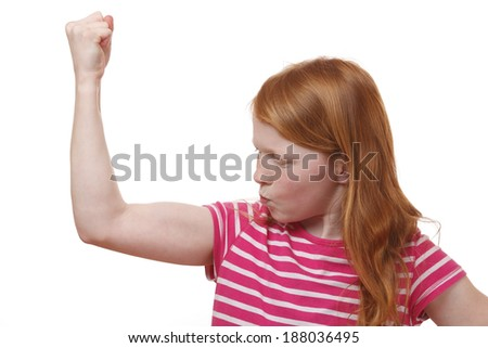 Young red-haired girl shows muscles - stock photo