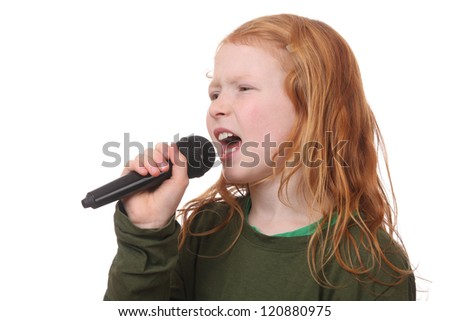 Young red haired girl singing into microphone on white background - stock photo