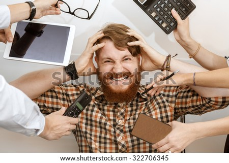 Young red-haired guy had a hard work day in the office - stock photo