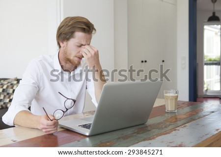 young red-haired man sitting at table with his laptop and having a headache - stock photo