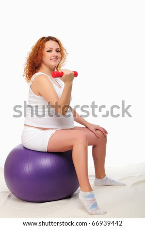 Young red-haired pregnant girl is engaged in sports. - stock photo