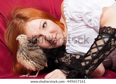 Young red-haired woman and a live quail