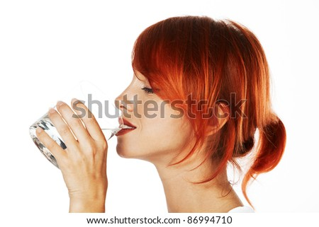 young red haired woman is drinking mineral water - stock photo