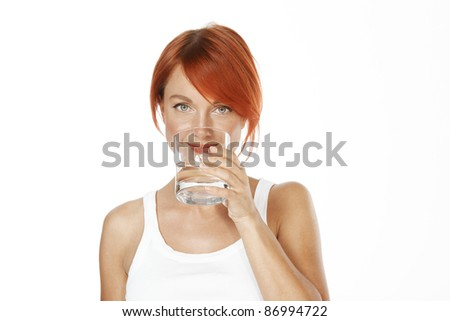 young red haired woman is drinking mineral water