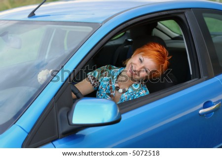 Young red-haired woman is siting in a blue car. Woman is happy - stock photo