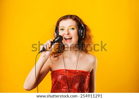Young red-haired woman with microphone. Singer. Karaoke  - stock photo