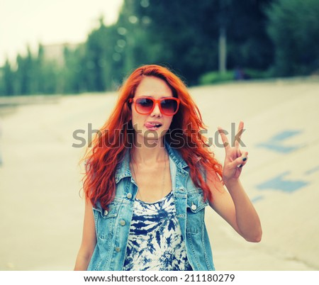 Young red haired women sticking her tongue out and show victory sign - stock photo