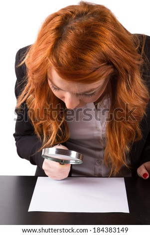 Young red head business woman holding magnifying glass on a paper, isolated on white background. - stock photo