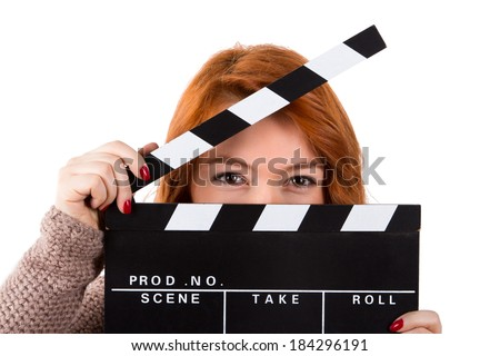 Young red head woman holding and showing black clapboard, isolated on white background. - stock photo
