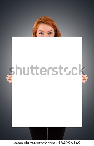 Young red head woman holding and showing blank, white advertisement board on dark background. - stock photo